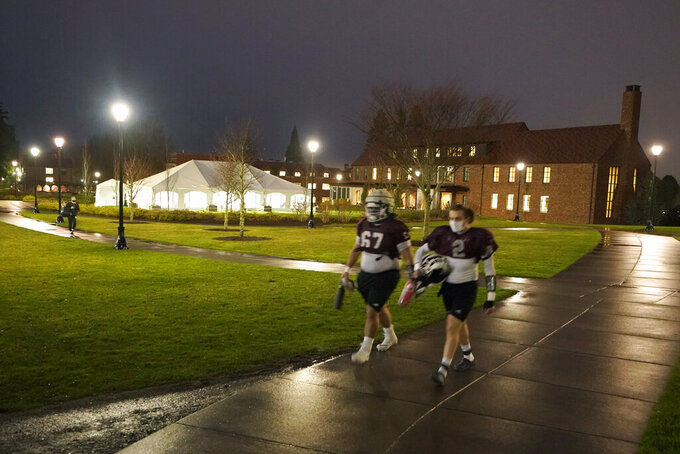 Two players walk near a large white tent used for COVID-19 testing as they head to a field for NCAA college football practice at the University of Puget Sound, Tuesday, Feb. 2, 2021, in Tacoma, Wash. School athletics officials are fully aware one infection could derail the season. (AP Photo/Ted S. Warren)