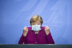 German Chancellor Angela Merkel holds her face mask as she arrives for a press conference after a meeting with the governors of the German states in Berlin Germany, Wednesday, Oct. 14, 2020. (Stefanie Loos/Pool Photo via AP)