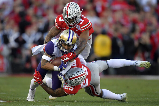 Washington wide receiver Andre Baccellia, middle, is tackled by Ohio State cornerback Damon Arnette top, and safety Brendon White during the first half of the Rose Bowl NCAA college football game Tuesday, Jan. 1, 2019, in Pasadena, Calif. (AP Photo/Mark J. Terrill)