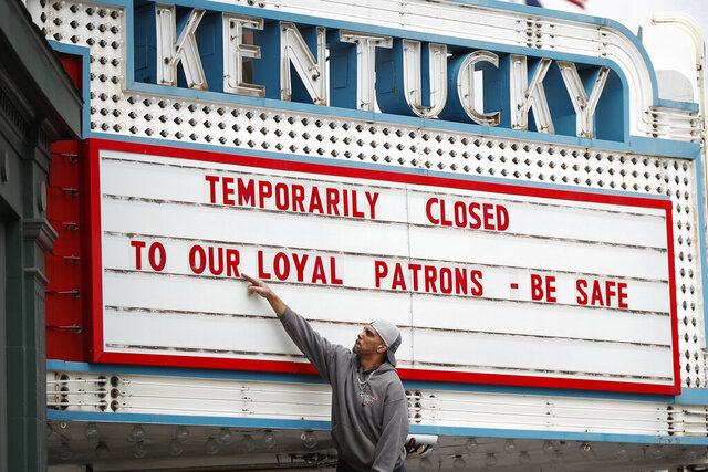 Harry Powell, of Lexington, Ky., works to change the marquee at the Kentucky Theatre in Lexington, Ky., Wednesday, March 18, 2020. The Kentucky Theatre will close on Wednesday following an executive order from Gov. Andy Beshear asking all public-facing businesses to close to help fight the spread of coronavirus. (Alex Slitz/Lexington Herald-Leader via AP)