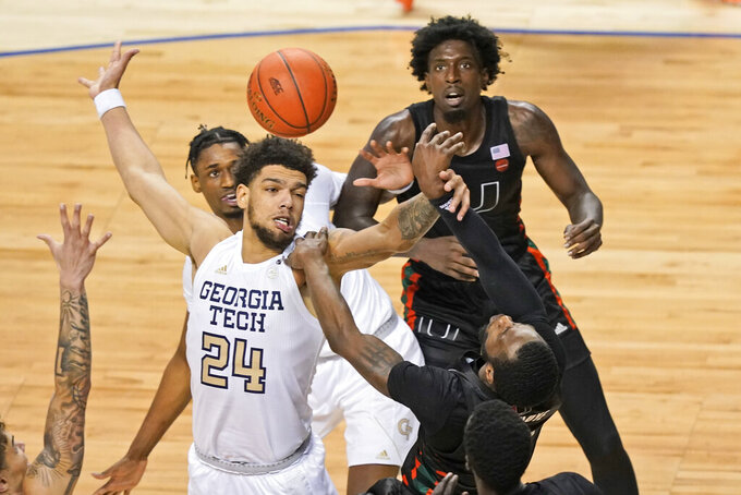 Georgia Tech forward Rodney Howard (24) and Miami guard Elijah Olaniyi, right, battle for a rebound as Miami center Nysier Brooks (3) looks on during the second half of an NCAA college basketball game in the quarterfinal round of the Atlantic Coast Conference tournament in Greensboro, N.C., Thursday, March 11, 2021. (AP Photo/Gerry Broome)