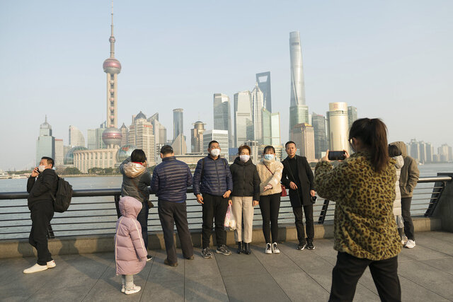 Visitors wearing protective face masks pose for a photo along the Bund in Shanghai, Thursday, Jan. 30, 2020. China counted 170 deaths from a new virus Thursday and more countries reported infections, including some spread locally, as foreign evacuees from China's worst-hit region returned home to medical observation and even isolation. (AP Photo)