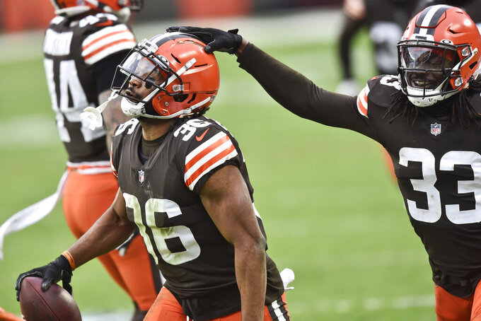 Cleveland Browns defensive back Ronnie Harrison (33) taps cornerback M.J. Stewart Jr. (36) on the helmet after Harrison intercepted a pass during the second half of an NFL football game against the Pittsburgh Steelers, Sunday, Jan. 3, 2021, in Cleveland. (AP Photo/David Richard)