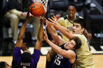 Northwestern guard Chase Audige (1) goes up for a rebound with center Ryan Young (15) and Purdue center Zach Edey (15) during the second half of an NCAA college basketball game in West Lafayette, Ind., Saturday, Feb. 6, 2021. (AP Photo/Michael Conroy)