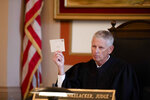 Judge Patrick T. Dinkelacker reads cards he said her received at his home during an execution of sentence of former judge Tracie Hunter on Monday, July 22, 2019 in Cincinnati. Hunter was ordered to serve a six-month jail sentence that was imposed more than four years ago. Hunter, 52, had gone to multiple courts to challenge her 2014 conviction and sentence on a felony count of unlawful interest in a public contract, which charged that she provided a confidential document to her brother when he faced a disciplinary hearing in his court job. (Albert Cesare/The Cincinnati Enquirer via AP)