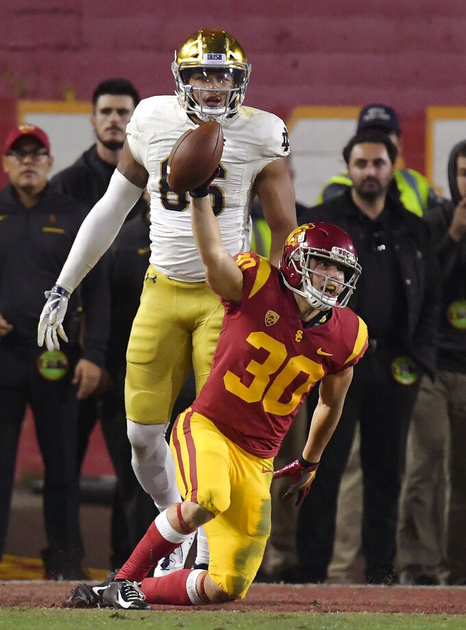 Southern California safety Jordan McMillan holds the ball up after intercepting a pass in the end zone that was intended for Notre Dame tight end Alize Mack, rear, during the second half of an NCAA college football game Saturday, Nov. 24, 2018, in Los Angeles. Notre Dame won 24-17. (AP Photo/Mark J. Terrill)