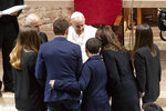 Pope Francis meets a family in the sanctuary of Greccio, Italy, Sunday, Dec. 1, 2019.  Pope Francis on Sunday hailed Nativity scenes as ''simple and admirable'' signs of Christian faith and encouraged their placement in workplaces, schools and town squares, as he bolstered a Christmas tradition that has at times triggered bitter legal battles in the United States.  (AP Photo/Alessandra Tarantino)