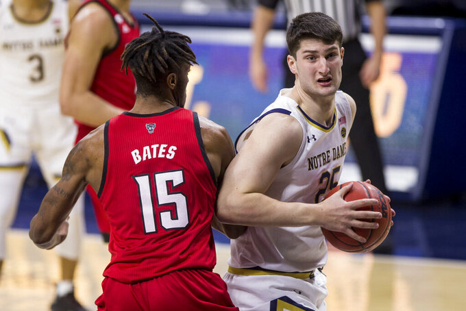 Notre Dame's Matt Zona (25) looks for a shot under the basket as North Carolina State's Manny Bates (15) defends during the second half of an NCAA college basketball game Wednesday, March 3, 2021, in South Bend, Ind. North Carolina State won 80-69. (AP Photo/Robert Franklin)