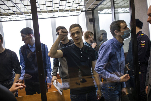 Members of a left-wing group Set (Network) attend a court hearing in Penza, Russia, Monday, Feb. 10, 2020. The court convicted seven members of the group of terrorism charges Monday and sentenced them to prison terms ranging from six to 18 years. (AP Photo/David Frenkel)