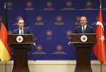 Turkey's Foreign Minister Mevlut Cavusoglu, right, smiles as he listens to Germany's Foreign Minister Heiko Maas, during their joint news conference following their meeting, in Ankara, Turkey, Monday, Jan. 18, 2021. The ministers met in the Turkish capital, following a tumultuous year in Turkish-European relations, expressing a desire to continue mending ties and solving an ongoing dispute between Turkey and Greece on maritime boundaries and energy rights in the Eastern Mediterranean. (Turkish Foreign Ministry via AP, Pool)