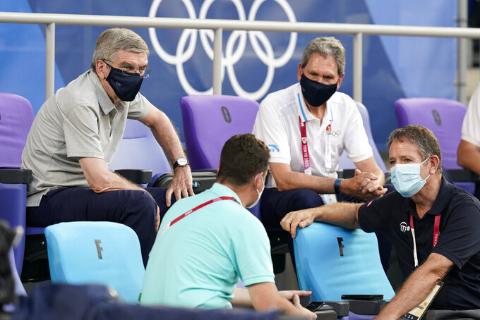 International Olympic Committee President Thomas Bach, left, speaks with guest during the men's single gold medal match of the tennis competition at the 2020 Summer Olympics, Sunday, Aug. 1, 2021, in Tokyo, Japan. (AP Photo/Patrick Semansky)