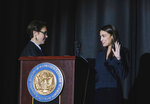Judge Jenny Rivera officiates the swearing-in ceremony of Congresswoman Alexandria Ocasio-Cortez at the Renaissance School for Musical Theater and Technology in the Bronx borough of New York on Saturday, Feb. 16, 2019. (AP Photo/Kevin Hagen)