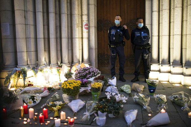 Police stand next to flowers and candles set on the steps of the Notre Dame church in Nice, France, Friday, Oct. 30, 2020. A new suspect is in custody in the investigation into a gruesome attack by a Tunisian man who killed three people in a French church. France heightened its security alert amid religious and geopolitical tensions around cartoons mocking the Muslim prophet. (AP Photo/Daniel Cole)