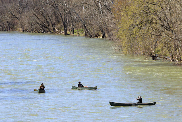 A group of kayakers practice social distancing while floating down the Greenbrier River Thursday, March 26, 2020 in Ronceverte, W.Va. Greenbrier County Health Department reported it's first COVID-19 case in the county Thursday. (Jenny Harnish/The Register-Herald via AP)