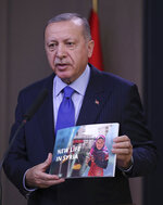 Turkish President Recep Tayyip Erdogan shows a document as he speaks to reporters before a visit to the United States, in Ankara, Turkey, Tuesday, Nov. 12, 2019.  Erdogan warned European nations Tuesday that his country could release all the Islamic State group prisoners it holds and send them to Europe, in response to EU sanctions over Cyprus.(Presidential Press Service via AP, Pool)