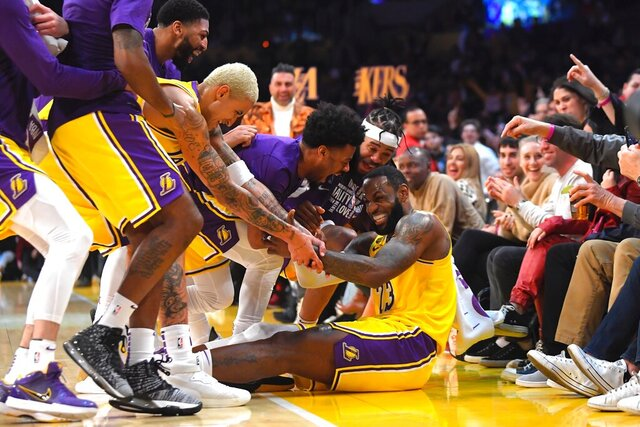 Los Angeles Lakers forward LeBron James I swarmed by teammates after making several 3-point shots in a row during the second half of the team's NBA basketball game against the San Antonio Spurs on Tuesday, Feb. 4, 2020, in Los Angeles. (AP Photo/Mark J. Terrill)