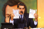 In this photo released by Venezuela's Miraflores presidential press office, President Nicolas Maduro shows what Venezuelan authorities claim are identification documents of former U.S. special forces and U.S. citizens Airan Berry, right, and Luke Denman, left, during a online press conference in Caracas, Venezuela, Wednesday, May 6, 2020. Maduro also touted a video showing a scruffy-looking Texas native Luke Denman, divulging details about a failed invasion as proof that U.S. authorities backed an attempt to forcibly remove him from power. (Miraflores Palace presidential press office via AP)
