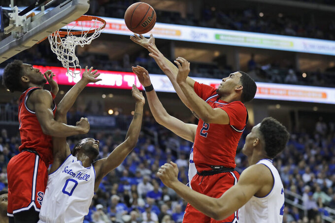 St. John's Julian Champagnie , top right, drives to the basket over Seton Hall defenders during the first half of an NCAA college basketball game in Newark, N.J., Sunday, Feb. 23, 2020. (AP Photo/Seth Wenig)