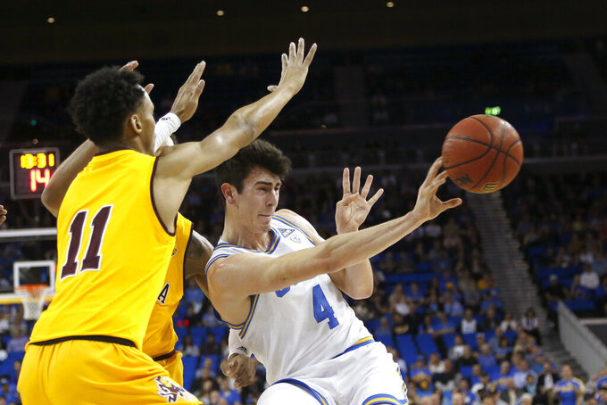 UCLA guard Jaime Jaquez Jr. (4) passes the ball while defended by Arizona State players, including guard Alonzo Verge (11), during the first half of an NCAA college basketball game Thursday, Feb. 27, 2020, in Los Angeles. (AP Photo/Ringo H.W. Chiu)