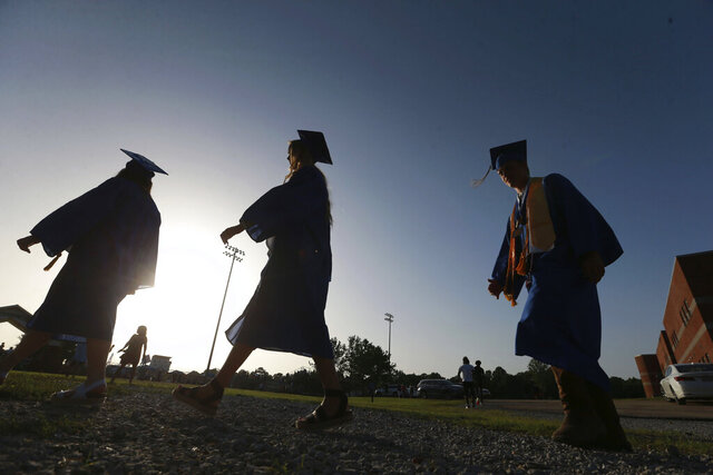 FILE - In this June 27, 2020, file photo, Saltillo High School seniors make their way to the football field as the sun begins to set for their graduation ceremony in Saltillo, Miss. The number of high school seniors applying for U.S. federal college aid plunged in the weeks following the sudden closure of school buildings this spring — a time when students were cut off from school counselors, and families hit with financial setbacks were reconsidering plans for higher education. (Thomas Wells/The Northeast Mississippi Daily Journal via AP, File)