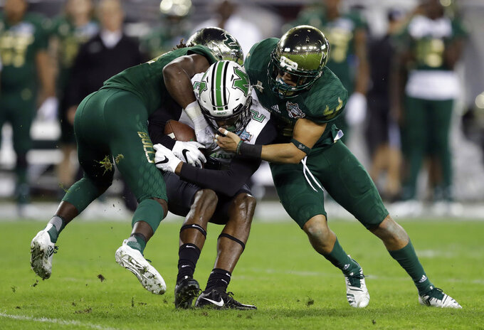 Marshall wide receiver Artie Henry III (2) is sandwiched by South Florida cornerback Ronnie Hoggins (19) and defensive back Nick Roberts (24) after a reception during the first half of the Gasparilla Bowl NCAA college football game Thursday, Dec. 20, 2018, in Tampa, Fla. (AP Photo/Chris O'Meara)