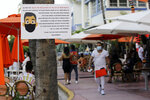 FILE - In this July 24, 2020, file photo, a sign informs customers at the Edison Hotel restaurant about wearing a protective face mask during the coronavirus pandemic, along Ocean Drive in Miami Beach, Fla. Families trying to get in a last-minute vacation before school starts better do some homework on COVID-19 restrictions before loading up the minivan. (AP Photo/Lynne Sladky, File)