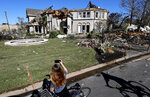 A passerby stops to look at a mansion damaged by a tornado in the Preston Hollow section of Dallas, Monday, Oct. 21, 2019. (AP Photo/LM Otero)