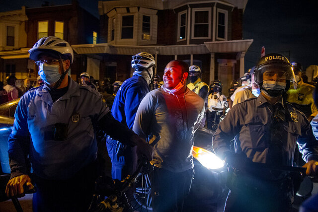 A person is handcuffed and detained by police at 55th and Pine Street, Wednesday, Oct. 28, 2020, in Philadelphia, after the citywide curfew had passed, two days after Walter Wallace Jr. was killed by police officers. (Tom Gralish/The Philadelphia Inquirer via AP)
