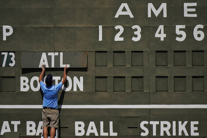 An attendance places the Atlanta Braves sign on the Green Monster score board before a spring training baseball game against the Boston Red Sox on Monday, March 1, 2021, in Fort Myers, Fla. (AP Photo/Brynn Anderson)
