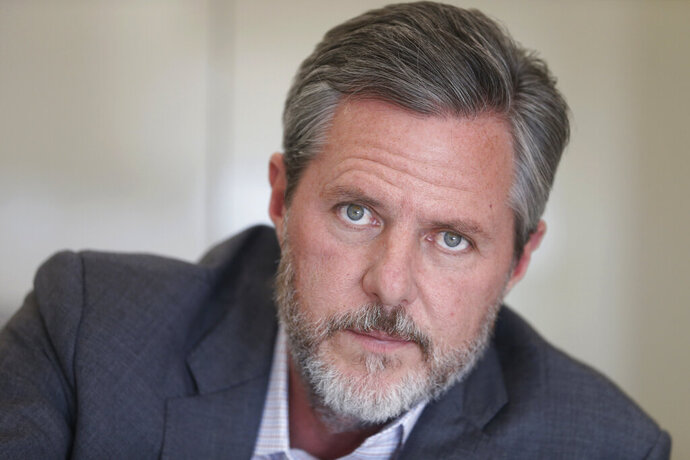 """FILE - In this Nov. 16, 2016, file photo, Liberty University president Jerry Falwell Jr., poses during an interview in his offices at the school in Lynchburg, Va. Falwell Jr. said Tuesday, Sept. 10, 2019, that he is asking the FBI to investigate what he called a """"criminal"""" smear campaign orchestrated against him by several disgruntled former board members and employees. (AP Photo/Steve Helber, File)"""