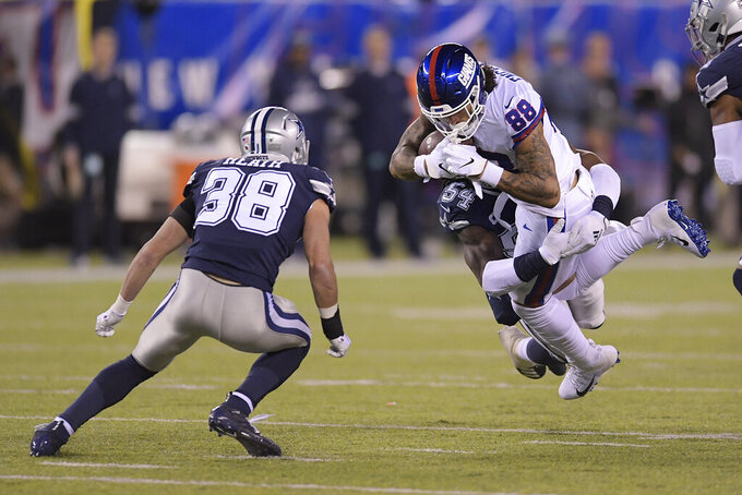 New York Giants tight end Evan Engram (88) is tackled by Dallas Cowboys middle linebacker Jaylon Smith (54) during the second quarter of an NFL football game, Monday, Nov. 4, 2019, in East Rutherford, N.J. (AP Photo/Bill Kostroun)