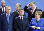 German Chancellor Angela Merkel, front right, speaks with French President Emmanuel Macron, front center, during a group photo at a conference on Libya at the chancellery in Berlin, Germany, Sunday, Jan. 19, 2020. Front left is Turkish President Recep Tayyip Erdogan. Back row left to right, European Council President Charles Michel, German Foreign Minister Heiko Maas and U.S. Secretary of State Mike Pompeo. (AP Photo/Michael Sohn)