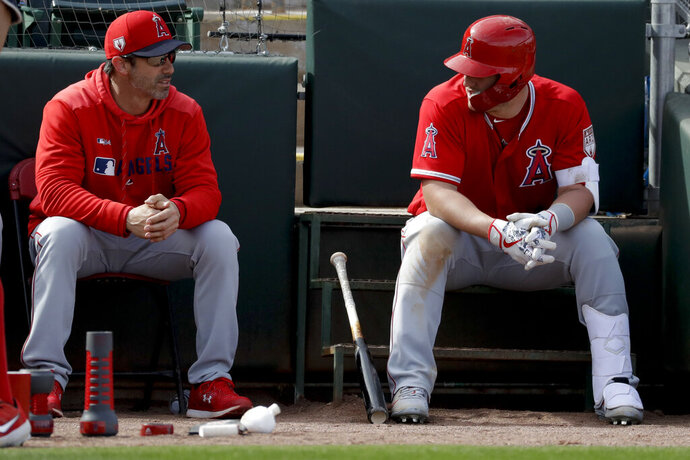 FILE - In this Tuesday, Feb. 26, 2019, file photo, Los Angeles Angels manager Brad Ausmus, left, talks with Mike Trout during the fourth inning of a spring baseball game against the Oakland Athletics in Mesa, Ariz. Trout has cemented himself in place as the Los Angeles Angels' cornerstone with his $432 million contract. The Angels are already hard at work building a championship team on his shoulders.(AP Photo/Chris Carlson, File)