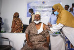 Dr. Maxamed Maxamuud Fuje receives a shot of AstraZeneca COVID-19 vaccine, manufactured by the Serum Institute of India and provided through the global COVAX initiative, at a ceremony to mark the start of coronavirus vaccinations in Mogadishu, Somalia Tuesday, March 16, 2021. (AP Photo/Farah Abdi Warsameh)