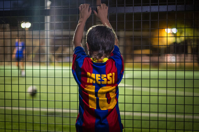 Un niño con una camiseta de Lionel Messi observa un partido de fútbol en Banyoles, España, el miércoles 2 de septiembre de 2020. (AP Foto/Emilio Morenatti)