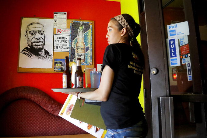 In this June 7, 2020, photo, a portrait of George Floyd hangs in the lobby of Conga Latin Bistro, a Minneapolis club where he worked as a bouncer. His coworker Princis Mercedes carries drinks for customers. (AP Photo/Julio Cortez)