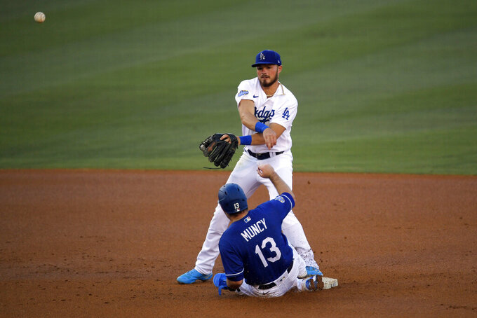 Los Angeles Dodgers' Max Muncy, below, is forced out at second asGavin Lux attempts to throw out A.J. Pollock at first during an intrasquad baseball game Wednesday, July 15, 2020, in Los Angeles. Pollock was safe at first. (AP Photo/Mark J. Terrill)
