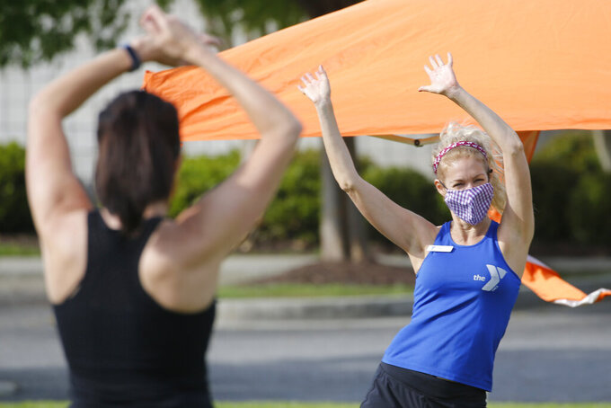 Zumba Gold instructor, Stacey Zebrowski, right, leads a class at the Shady Grove YMCA Friday May 15, 2020, in Glen Allen, Gov. Ralph Northam instituted a phase one reopening of certain portions of the state Friday. (AP Photo/Steve Helber)