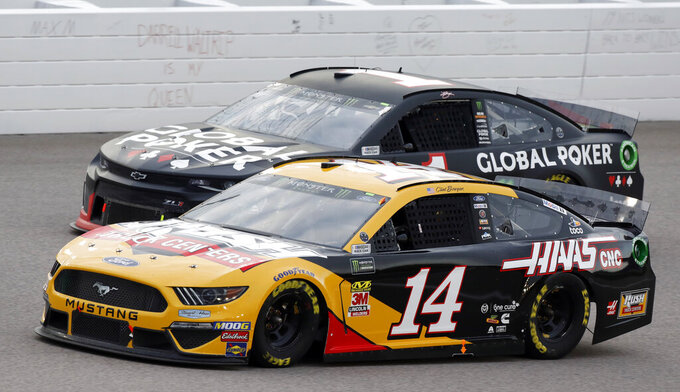 Clint Bowyer (14) drives next to Kurt Busch during the NASCAR Cup Series auto race at Kansas Speedway in Kansas City, Kan., Saturday, May 11, 2019. (AP Photo/Colin E. Braley)