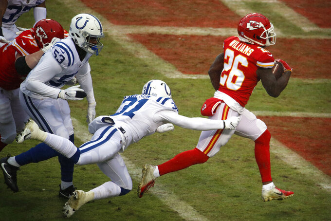 Kansas City Chiefs running back Damien Williams (26) scores a touchdown away from Indianapolis Colts cornerback Quincy Wilson (31) during the first half of an NFL divisional football playoff game in Kansas City, Mo., Saturday, Jan. 12, 2019. (AP Photo/Charlie Riedel)