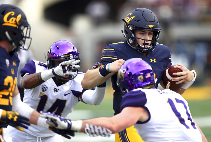 California quarterback Chase Garbers, right, is chased out of bounds by Washington's JoJo McIntosh (14) and Tevis Bartlett (17) during the first half of an NCAA college football game Saturday, Oct. 27, 2018, in Berkeley, Calif. (AP Photo/Ben Margot)