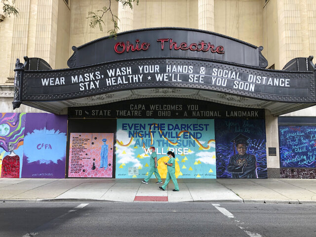 FILE — In this Aug. 26, 2020 file photo, workers in scrubs and masks walk by the Ohio Theatre in Columbus, Ohio, amid the coronavirus pandemic. (AP Photo/Julie Carr Smyth, File)