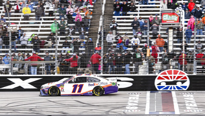 Denny Hamlin takes the checkered flag to win a NASCAR Cup auto race at Texas Motor Speedway, Sunday, March 31, 2019, in Fort Worth, Texas. (AP Photo/Larry Papke)