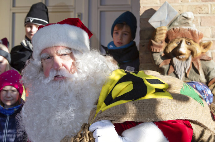 A man dressed as Santa Claus is welcomed by children during the opening of the most famous German Christmas mail office in the small village of Himmelpfort (Heaven's Door) north of Berlin, Germany, Thursday, Nov. 14, 2019. Santa Claus is at it again, answering thousands of Christmas letters from children around the world at a special post office in Himmelpfort. As part of the annual event organized by Germany's Deutsche Post, Santa and 20 helpers last year responded to 277,200 letters from 64 countries.  (Soeren Stache/dpa via AP)