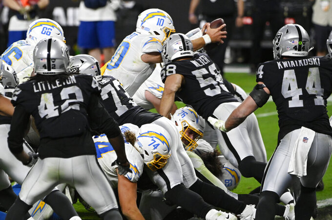 Los Angeles Chargers quarterback Justin Herbert (10) scores a touchdown against the Las Vegas Raiders in overtime of an NFL football game, Thursday, Dec. 17, 2020, in Las Vegas. (AP Photo/David Becker)