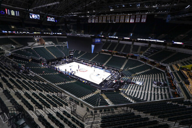 FILE - In this March 12, 2020, file photo, the seating area at Bankers Life Fieldhouse is viewed in Indianapolis after the Big Ten Conference announced that remainder of the men's NCAA college basketball games tournament was canceled. Indianapolis city leaders want the college basketball world to know it is open for business. On Friday, Sept. 18, 2020, Indiana Sports Corp, a local, year-round organizing committee, publicly released a 16-page proposal to convert convert about half of the city convention center's exhibition halls and meeting rooms into basketball courts and locker rooms, providing expansive safety measures and daily COVID-19 testing. (AP Photo/Michael Conroy, File)