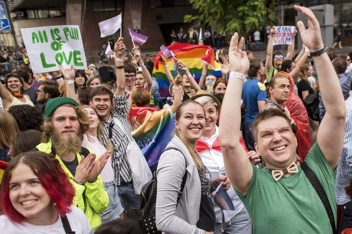 Gay and lesbian rights activists march during the annual Gay Pride parade, protected by riot police in Kiev, Ukraine, Sunday, June 17, 2018. Several thousand supporters of gay pride have held a march in Ukrainian capital that lasted about 20 minutes despite opponents attempts to block them. (AP Photo/Evgeniy Maloletka)