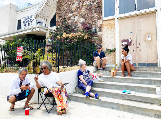 From right, Stephanie Serra and her husband Chase Cole sit at the top of the steps of First Baptist Church of Venice while talking to Ingrid Mueller, center, on Sunday, July 11, 2021, in Los Angeles as Naomi Nightingale, left, speaks with a visitor from her lawn chair before returning to the conversation. The group meets here every other Sunday to discuss ways to preserve the abandoned church building.  (Alejandra Molina/RNS via AP)
