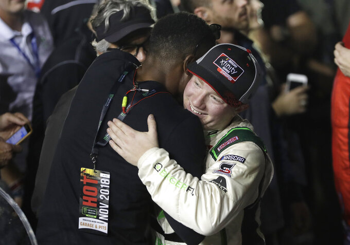 Tyler Reddick, right, is hugged after winning the NASCAR Xfinity Series championship auto race at the Homestead-Miami Speedway, Saturday, Nov. 17, 2018, in Homestead, Fla. (AP Photo/Lynne Sladky)