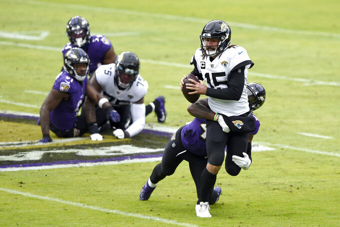 Jacksonville Jaguars quarterback Gardner Minshew II (15) is sacked by Baltimore Ravens linebacker Patrick Queen during the first half of an NFL football game, Sunday, Dec. 20, 2020, in Baltimore. (AP Photo/Gail Burton)